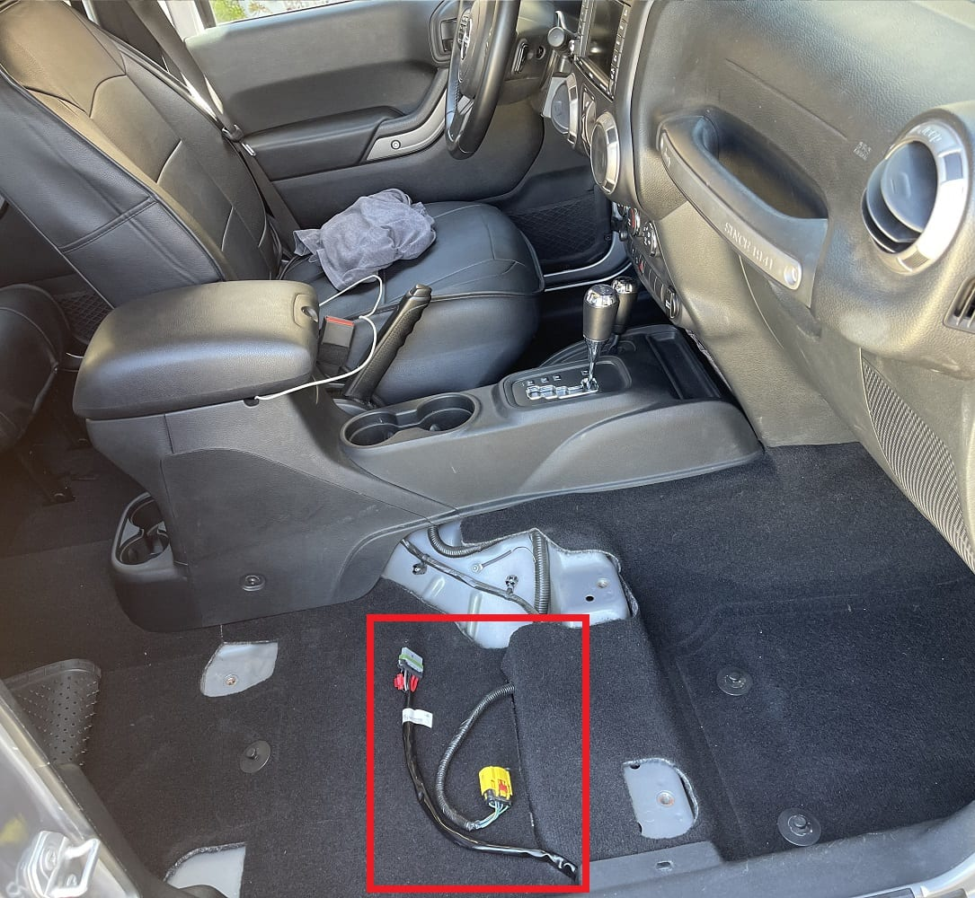 Running the wire under the carpet, to the area under the JK Wrangler passenger seat.